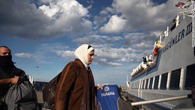 Syrian refugees board a boat bound for Turkey at a port in Kyrenia, Cyprus, on Sunday, November 23. Some 220 Syrian migrants crammed onto a fishing boat were rescued by a cruise ship off Cyprus' northern coast after their vessel hit rough seas in the Mediterranean Sea, authorities said.