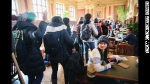 Washington University students march through a student lounge on the St. Louis campus as part of a nationwide