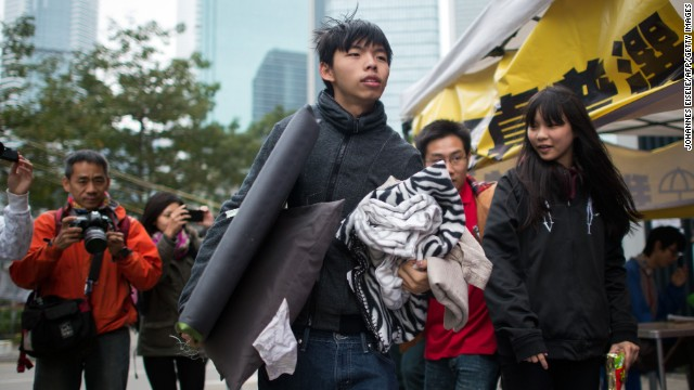 Student protest leader <a href='http://www.cnn.com/2014/12/01/world/asia/hong-kong-protest-joshua-wong-hunger-strike/'>Joshua Wong</a> carries his belongings toward a tent at the main protest site in Hong Kong's Admiralty district on Tuesday, December 2. Wong and two other student demonstrators have begun a hunger strike to demand discussions with Hong Kong's leaders over political reform for the city.