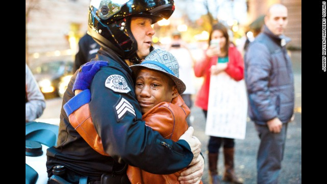 <strong>November 25:</strong> Police Sgt. Bret Barnum hugs 12-year-old Devonte Hart at a Portland, Oregon, rally showing support for the protesters in Ferguson, Missouri.