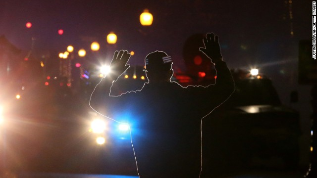 <strong>November 24:</strong> A protester in Ferguson, Missouri, stands in front of police vehicles with his hands up. A grand jury's decision not to indict police officer Darren Wilson for the killing of Michael Brown prompted <a href='http://www.cnn.com/2014/11/24/justice/gallery/ferguson-reaction/index.html'>new waves of protests in Ferguson</a> and across the country.