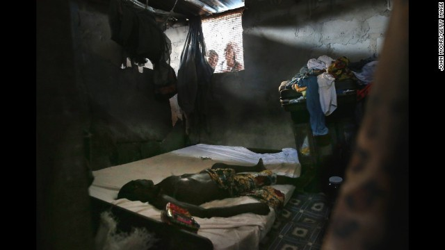 <strong>October 17:</strong> People peer into a bedroom as an Ebola victim's body awaits a burial team in Monrovia, Liberia.