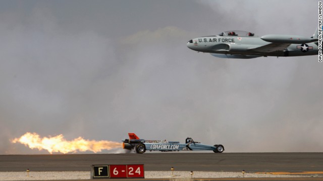 <strong>March 21:</strong> A Lockheed T-33 Shooting Star flies past the Smoke-N-Thunder jet car during a race between the two at the Los Angeles County Air Show.