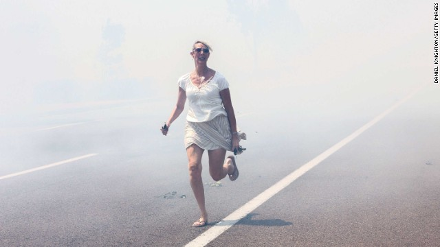 <strong>May 14:</strong> A woman flees a wildfire as it crosses a highway in Carlsbad, California. <a href='http://www.cnn.com/2014/05/13/us/gallery/california-wildfire/index.html'>Wildfires forced evacuations in San Diego County</a> after a high-pressure system brought unseasonable heat and gusty winds to the parched state.