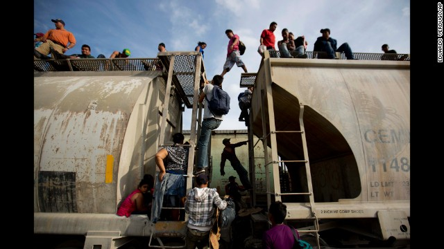 <strong>July 12:</strong> Central American migrants climb on a train in Ixtepec, Mexico, during their journey toward the U.S.-Mexico border. Days later, Texas Gov. Rick Perry announced that he would deploy up to 1,000 National Guard troops to the border, where <a href='http://ift.tt/WMeCpx'>tens of thousands of unaccompanied minors</a> have crossed into the United States this year.