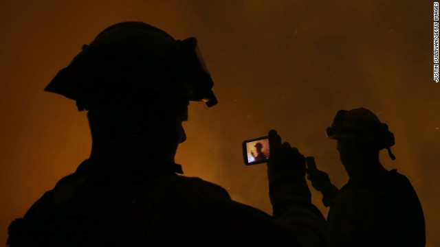 <strong>September 17: </strong>Firefighters take pictures with their cell phones as they monitor a backfire in Fresh Pond, California. California Gov. Jerry Brown declared a state of emergency where <a href='http://ift.tt/1mjCtIs'>wildfires torched tens of thousands of acres.</a>