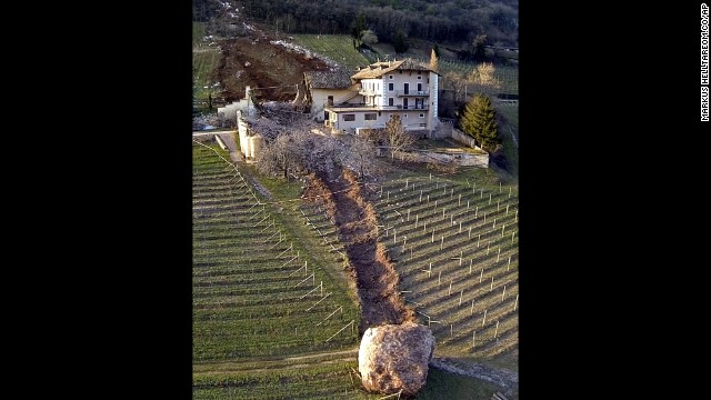 <strong>January 23:</strong> A trail of destruction is seen behind a boulder after a landslide in Ronchi di Termeno, Italy. The boulder missed the farmhouse at right but destroyed a barn before stopping in a vineyard. According to reports, the family living at the house was unharmed.