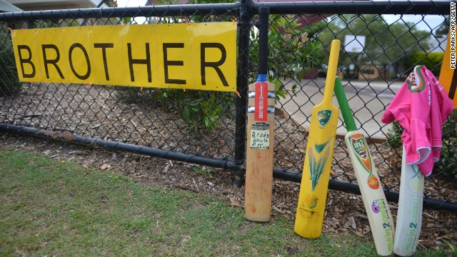 Cricket bats and signs are placed outside St. Patrick's Primary School hours before the funeral of Australian batsman Phil Hughes.