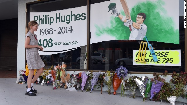 A schoolgirl walks past a tribute to Australian batsman Phil Hughes before his funeral to be held in his home town of Macksville.