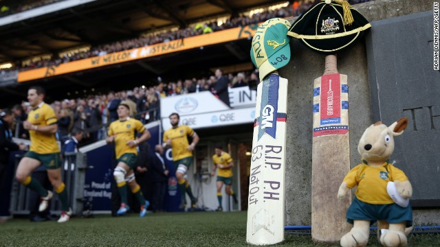 The Australian rugby team run onto the pitch beside a cricket bat and Australian mascot left in tribute to Australian cricketer Phil Hughes at Twickenham Stadium, southwest of London on November 29.