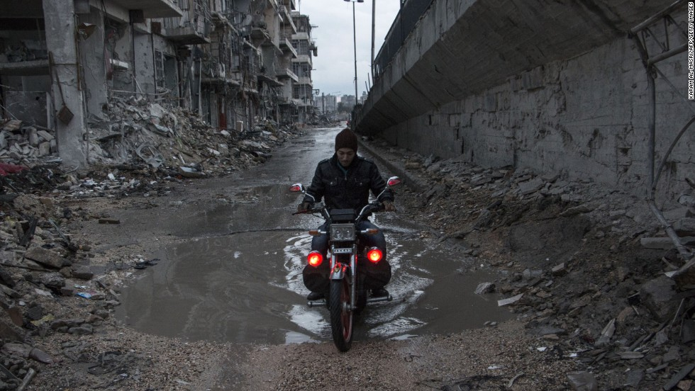 A man drives his motorcycle through a puddle in Aleppo, Syria, on Wednesday, November 26. The United Nations estimates more than 190,000 people have been killed in Syria since an uprising in March 2011 spiraled into civil war.