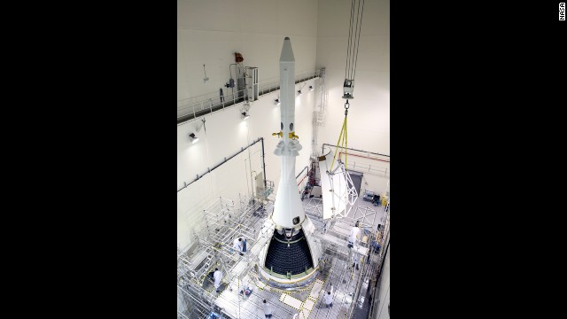Workers finish wrapping Orion in protective panels for its first flight. The panels protect the crew module from sound and vibration during launch.