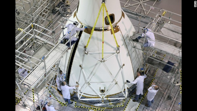 Workers check Orion after its last major assembly operations are completed -- the installation of protective panels around the spacecraft just below the Launch Abort System tower.