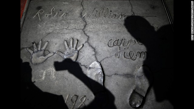 """<strong>August 12:</strong> Following the death of actor Robin Williams, people photograph his handprints and footprints at TCL Chinese Theater in Los Angeles. Williams, <a href='http://www.cnn.com/2014/08/11/showbiz/gallery/robin-williams/index.html'>a brilliant shapeshifter</a> who could channel his frenetic energy into delightful comic characters like """"Mrs. Doubtfire"""" or harness it into richly nuanced work like his Oscar-winning turn in """"Good Will Hunting,"""" <a href='http://www.cnn.com/2014/08/14/showbiz/robin-williams-parkinsons-disease/index.html'>committed suicide</a> at his home in the San Francisco Bay Area. He was 63."""