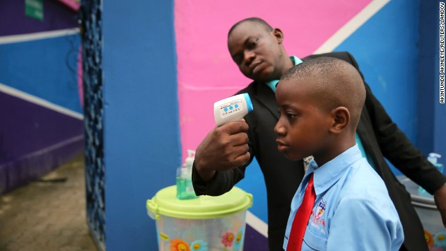 <strong>September 22:</strong> Amid the Ebola scare in West Africa, a school official in Lagos, Nigeria, takes a student's temperature with an infrared laser thermometer. Health officials say <a href='http://www.cnn.com/2014/04/04/world/gallery/ebola-in-west-africa/index.html'>the Ebola outbreak in West Africa</a> is the deadliest ever. More than 5,600 people have died there, according to the World Health Organization.