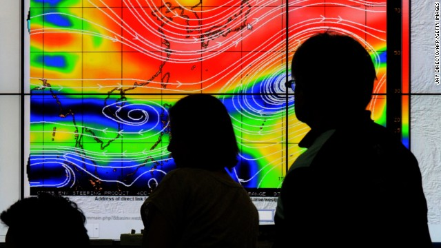 Meteorologists from the Philippine Atmospheric, Geophysical and Astronomical Services Administration (PAGASA) monitor and plot the direction of super typhoon Hagupit on December 4, 2014.