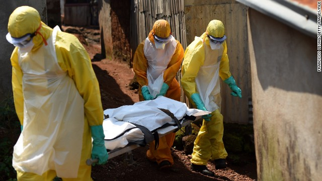 Health workers from Sierra Leone's Red Cross Society Burial Team carry a corpse out of a house in Freetown.