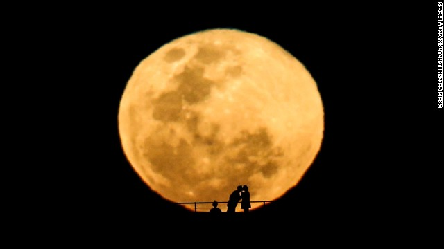 <strong>September 9:</strong> A couple kiss during a perigee moon, also known as a