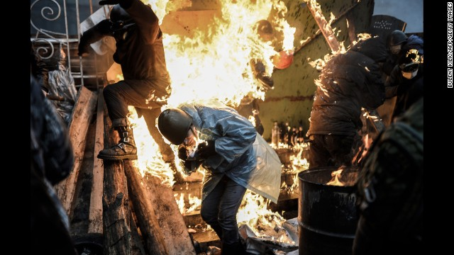 <strong>February 20:</strong> Protesters in Kiev, Ukraine, catch fire as they stand behind burning barricades during clashes with police. Kiev's Independence Square had been the center of <a href='http://www.cnn.com/2014/02/19/world/gallery/ukraine-protests-0218/index.html'>anti-government protests </a>since November 2013, when President Viktor Yanukovych reversed a decision on a trade deal with the European Union and instead turned toward Russia.