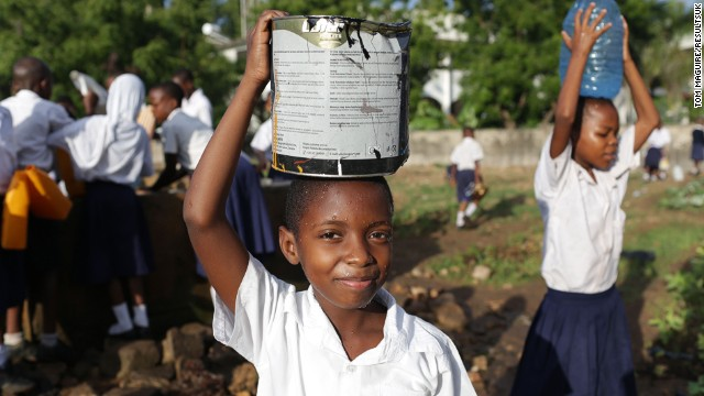 A child carries a pale of water for her crops.