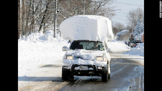 <strong>November 19:</strong> A vehicle with a large chunk of snow on its roof drives along Route 20 after a massive snowfall in Lancaster, New York. <a href='http://www.cnn.com/2014/11/19/us/gallery/wintry-weather/index.html'>A ferocious storm</a> dumped large piles of snow on parts of upstate New York, trapping residents in their homes and stranding motorists on roadways.