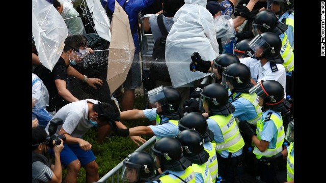 "<strong>September 28:</strong> Riot police use pepper spray as they clash with pro-democracy protesters outside the government headquarters in Hong Kong. <a href='http://www.cnn.com/2014/09/22/asia/gallery/hong-kong-students-protest/index.html'>Demonstrations began</a> in response to China's decision to allow only Beijing-vetted candidates to stand in the city's 2017 election for chief executive. Protesters say Beijing has gone back on its pledge to allow universal suffrage in Hong Kong, which was promised ""a high degree of autonomy"" when it was handed back to China by Britain in 1997. The umbrella has become the defining image of the protest movement, used to shield protesters from tear gas and the elements."