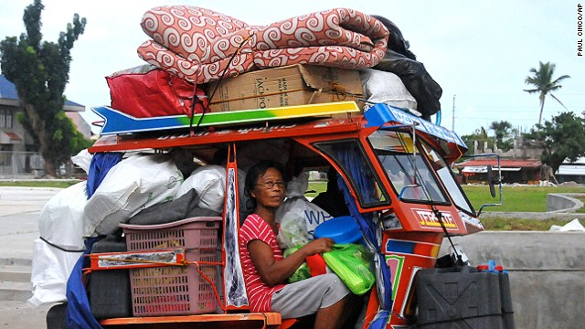 A woman from Tanauan township boards a tuk tuk carrying her belongings in anticipation of Typhoon Hagupit.