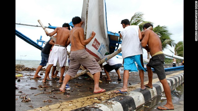 Fishermen carry their outrigger to higher ground in Legazpi on Friday, December 5. More than 600,000 people had evacuated by Saturday morning, according to the National Disaster Risk Reduction and Management Council.