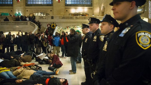 "Police stand guard as protesters participate in a ""die-in"" December 6 at Grand Central Station in New York."
