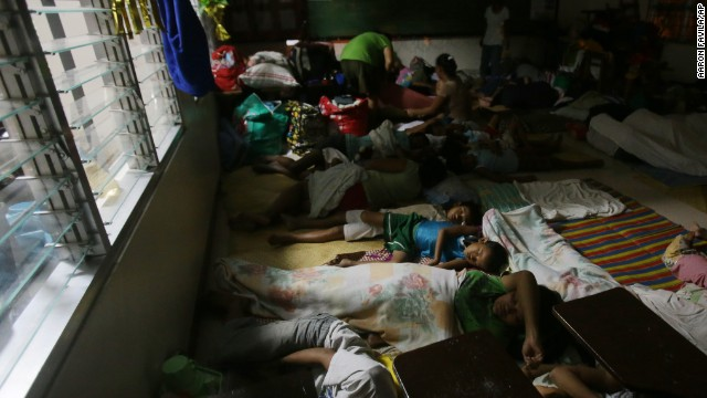 Families sleep at a school used as an evacuation center on December 6 in Legazpi.