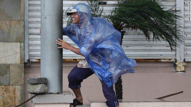 A man holds on as strong winds from Typhoon Hagupit hit Legazpi, Philippines, on December 7.