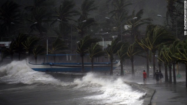 More than half a million people sought shelter across the Philippines as authorities stepped up preparation efforts ahead of the storm. Here, some people walk along the waterfront on December 7.