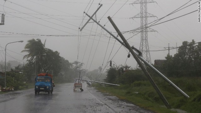 Motorists pass toppled utility poles in Camalig, Philippines, on December 7.