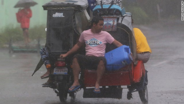 Residents head for an evacuation center on December 7 as strong winds and rains hit Legazpi.