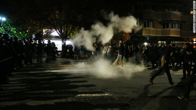 Demonstrators retreat in Berkeley, California, after police deploy tear gas during a protest that turned violent before dawn on December 7.