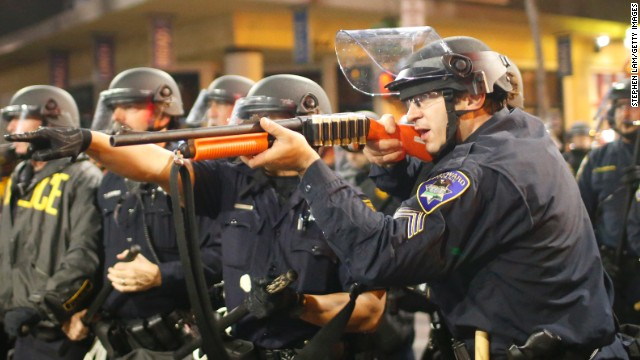 A police officer raises a shotgun toward the crowd in Berkeley on Saturday, December 6.