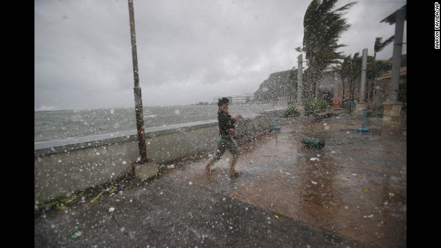 Strong winds and rain push a man around on the shore in Legazpi on December 7.