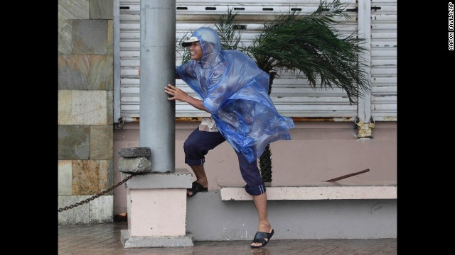A man holds on as strong winds from Typhoon Hagupit hit Legazpi on December 7.