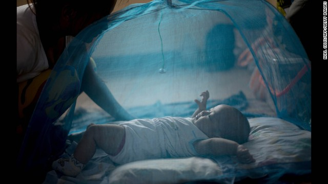 A mother watches her baby inside a mosquito net at an evacuation center in Manila on December 7.