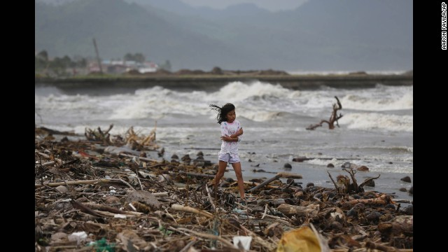 A girl walks along the shore as strong waves hit Atimonan, Philippines, on Saturday, December 6.