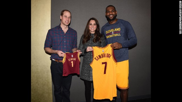 The royal couple poses with basketball star LeBron James after the game. Prince William is holding a jersey made for their son, Prince George.