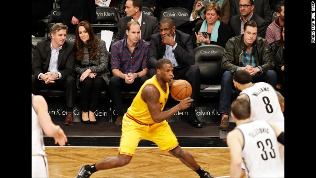 Prince William sits with former NBA star Dikembe Mutombo during the game.
