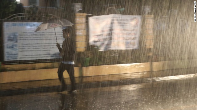 A man walks through heavy rain in San Juan, Philippines, on December 8.