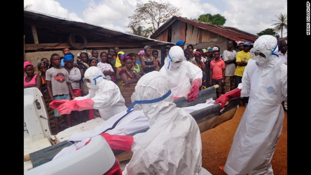 Ebola health care workers carry the body of a man suspected of dying from the Ebola virus in a small village on the outskirts of Monrovia, Liberia, on Friday, December 5.