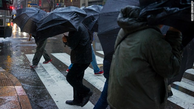 People carrying umbrellas cross a street in New York City on Tuesday, December 9.