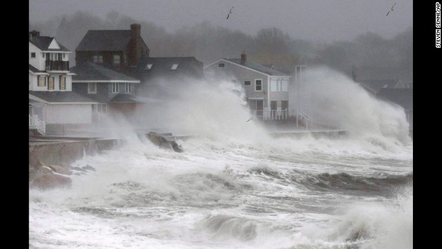 Waves splash against a seawall and onto houses in Scituate, Massachusetts, on December 9.