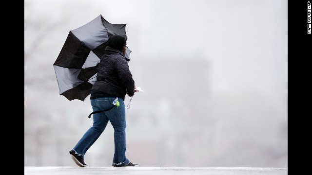 A woman's umbrella is blown back by winds in Philadelphia on December 9.