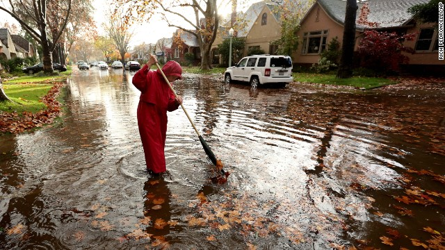 A woman stands in knee-deep water as she clears a clogged storm drain that had caused her street to flood in Sacramento, California, on Wednesday, December 3.