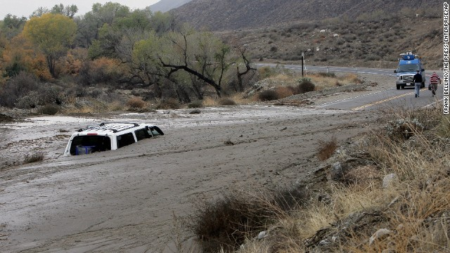 A television news crew walks away from a vehicle caught in an overnight mudslide in San Jacinto, California, on December 4.