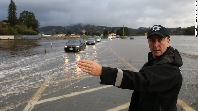 A police officer directs cars through a flooded section of a roadway December 3 in Mill Valley, California.